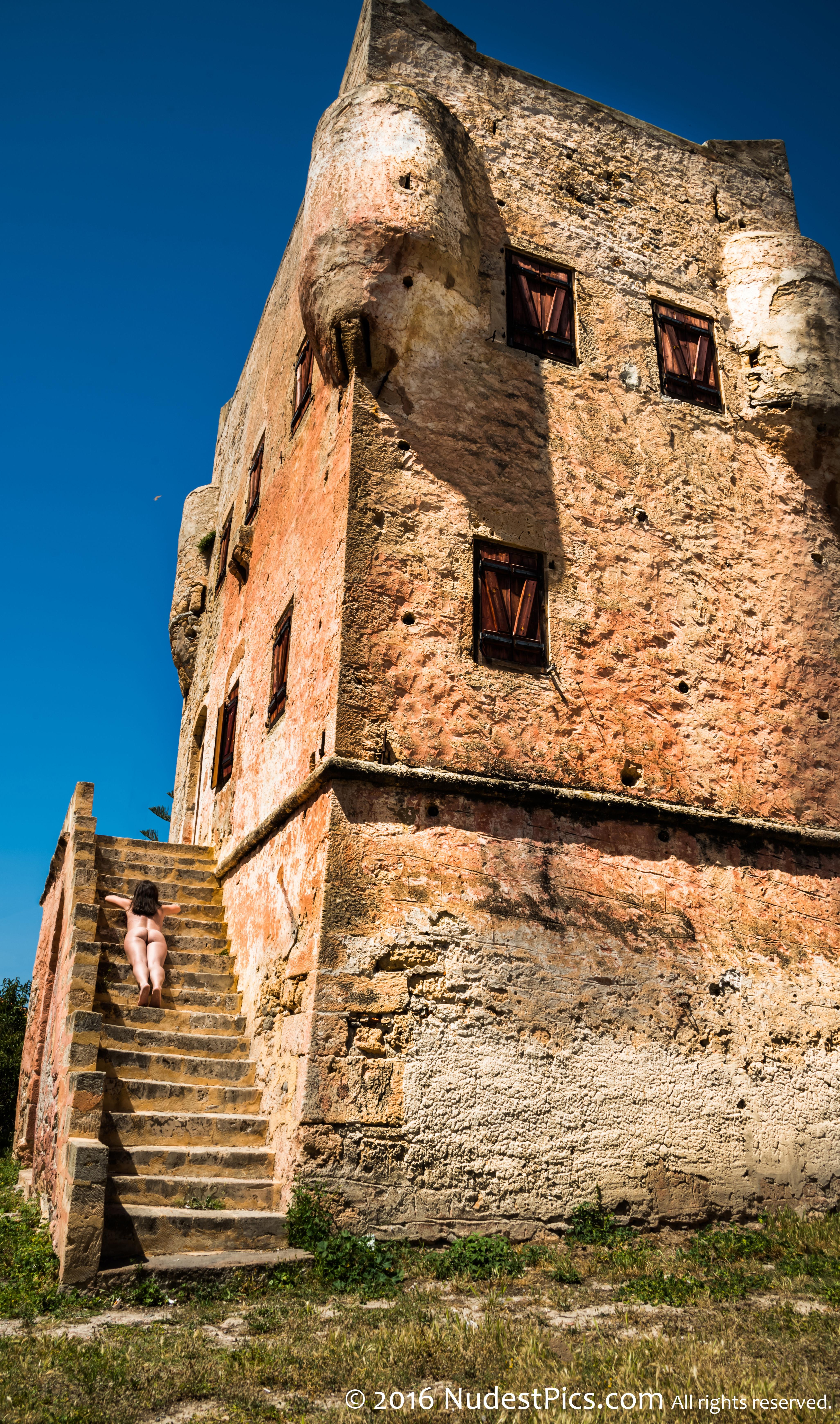 Nudist Gal Sunbathing on Medieval Tower's Stairs