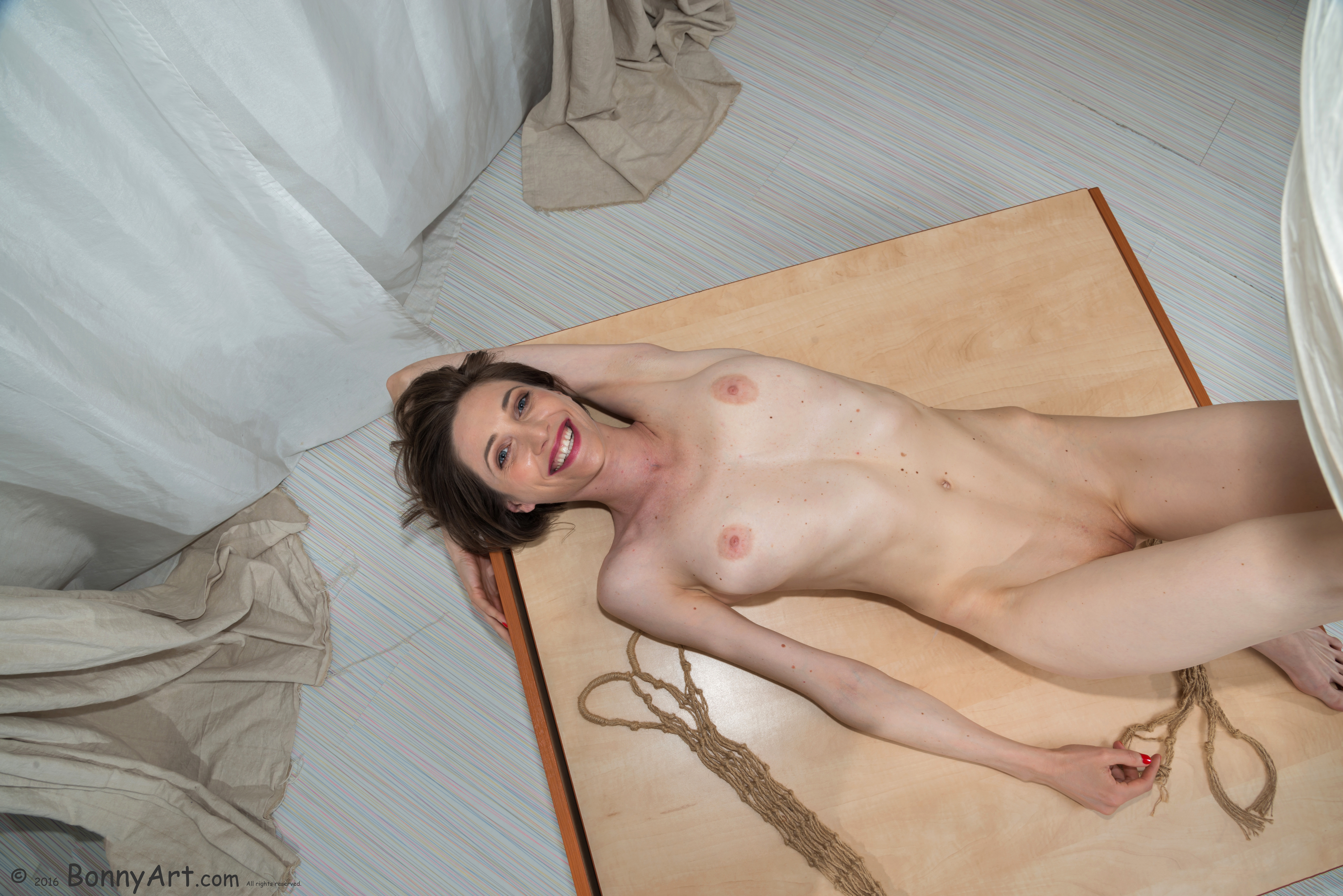 Happy Nude Skinny Woman on the Table