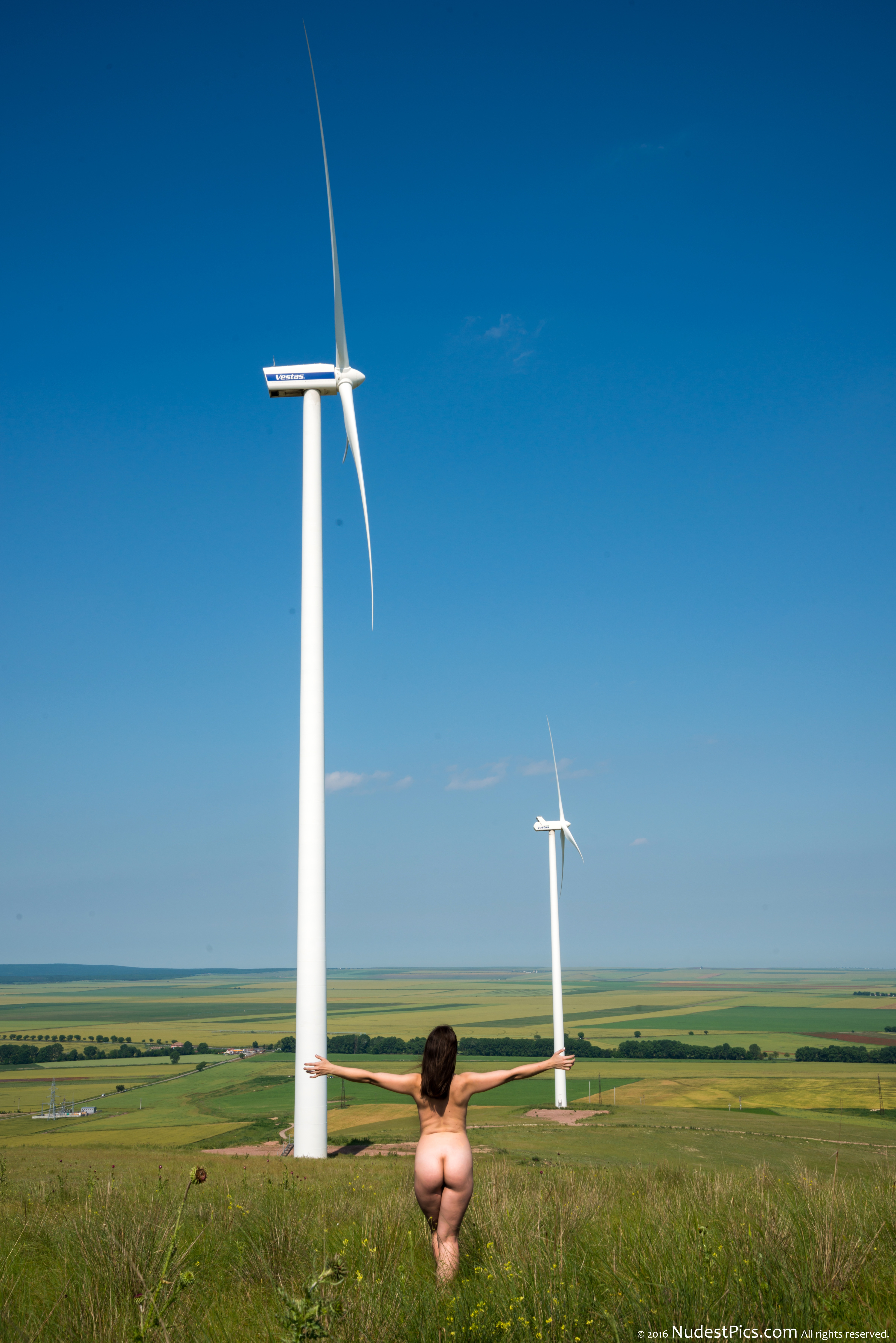 Nude Girl at the Wind Farm on Green Field