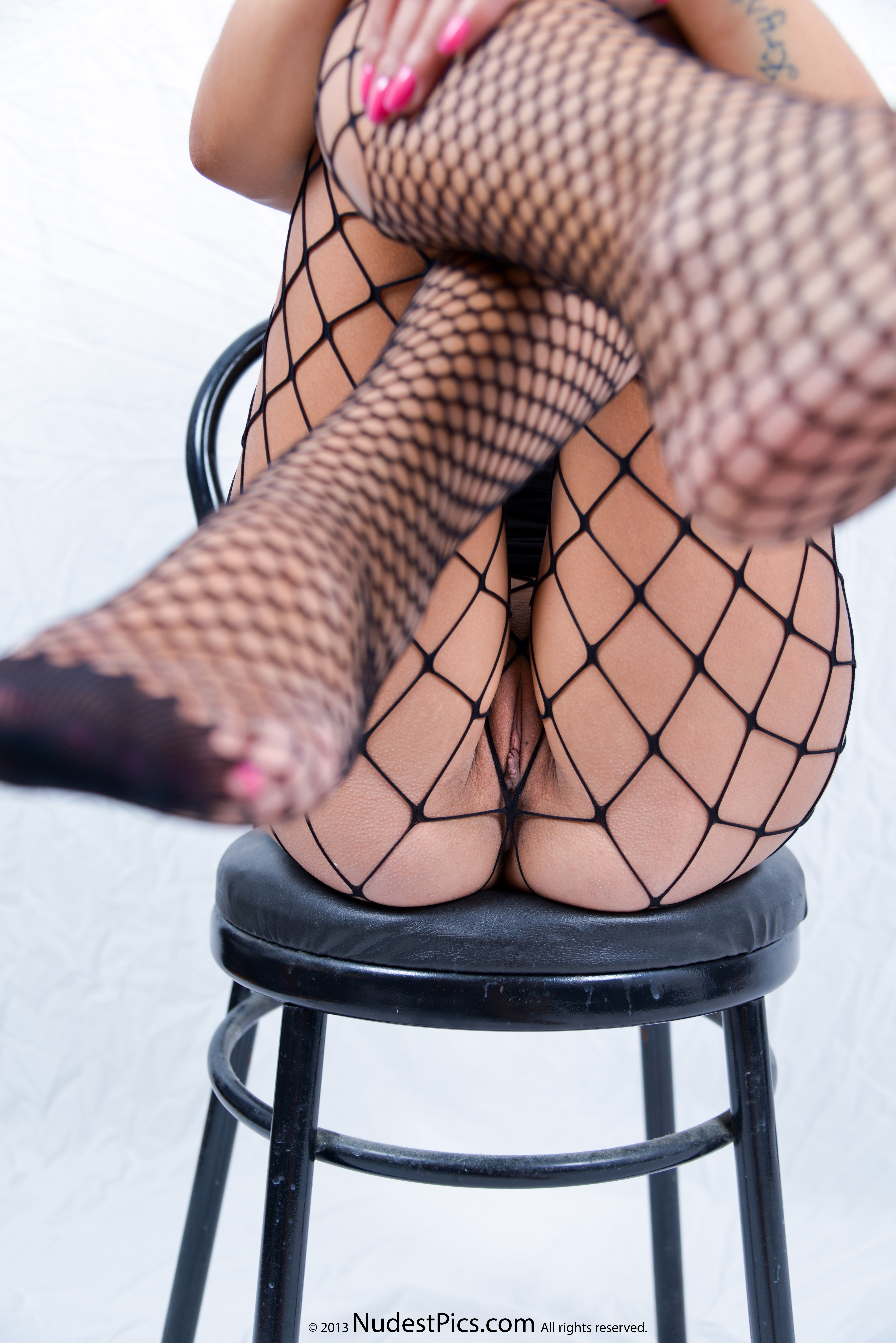 Pussy in Sexy Fishnets Crossing Legs Up on Chair