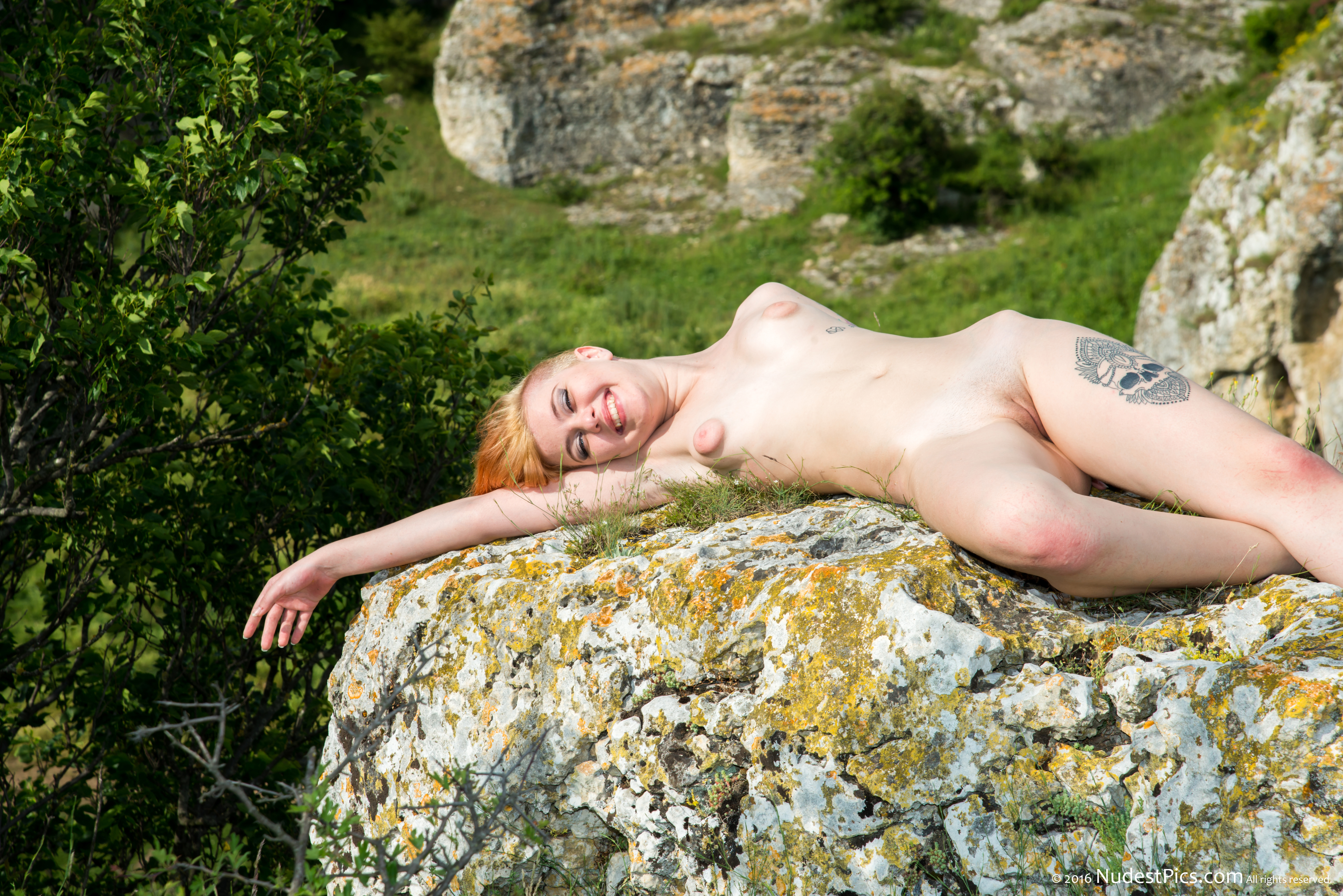 Cheerful Nudist Girl Sunbathing on a Rock