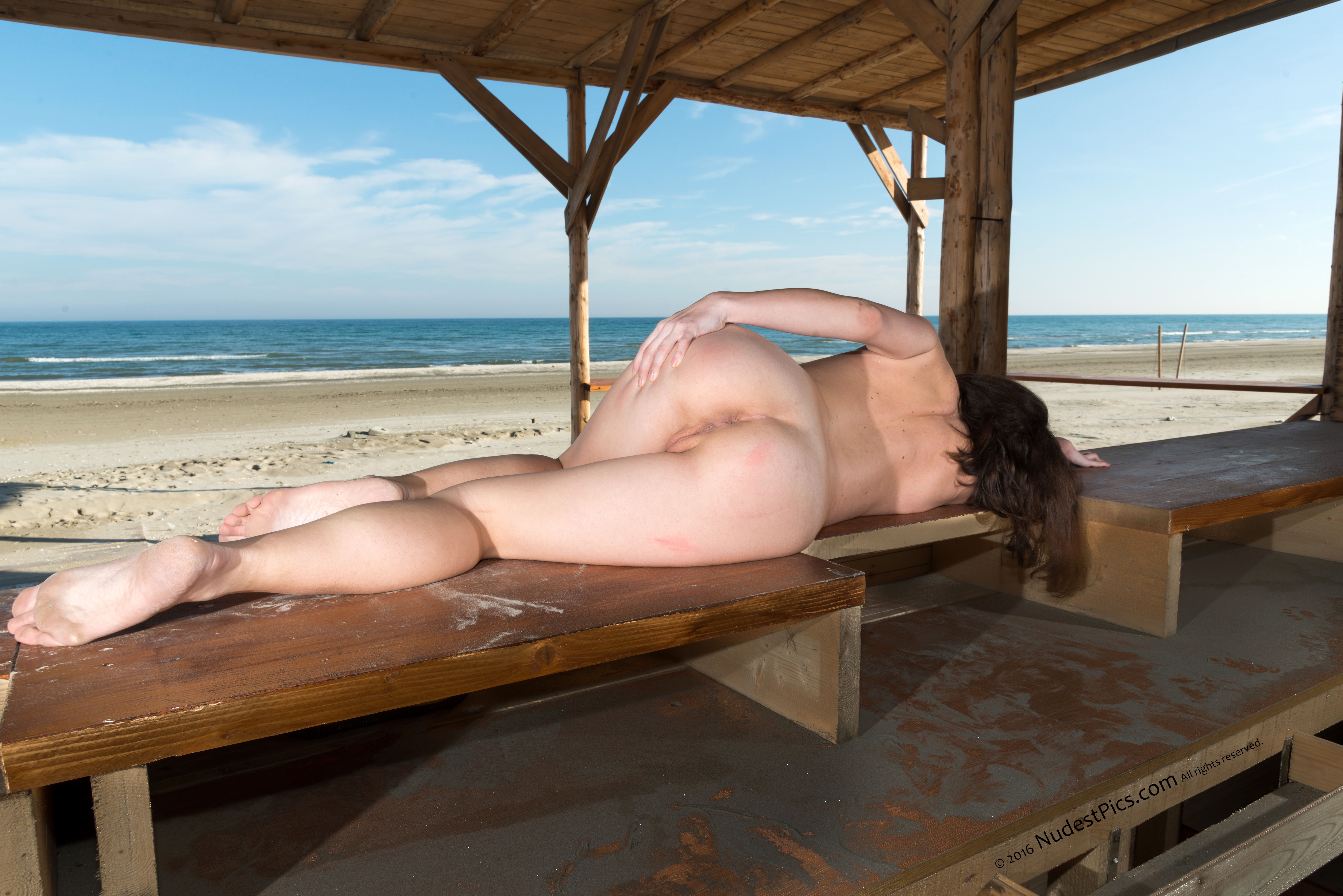 Nude Girl Laying from Behind on Dusty Beach Bar