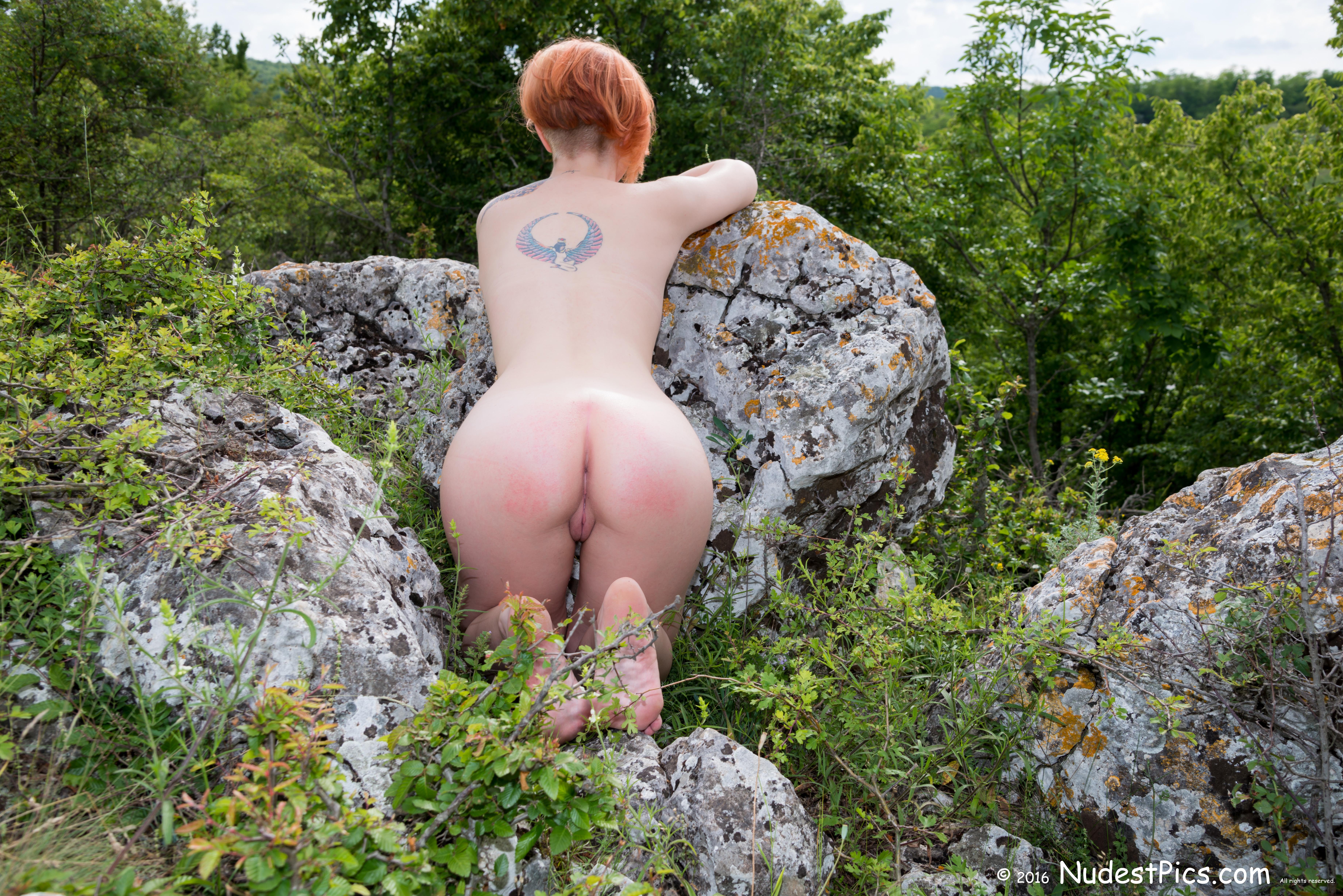 Naked Ginger Girl Kneeling at the Rocks